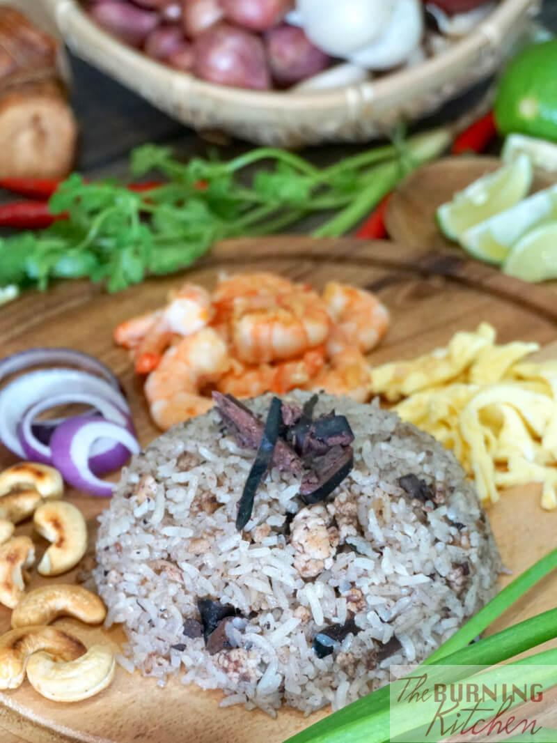 Thai Black Olive Fried Rice on wooden circular board with cashews, onions, prawns and fried cut egg