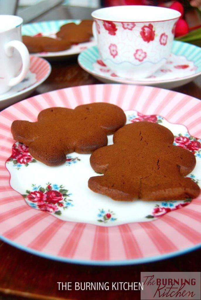 Plate of gingerbread man cookies on colourful plate with teacups in background